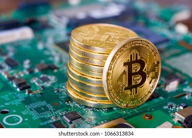 Bitcoins standing on the electronic motherboard of a laptop