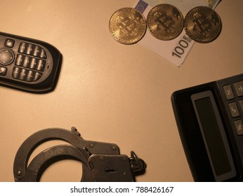 bitcoins, telephone, handcuffs, money, calculator on a wooden table