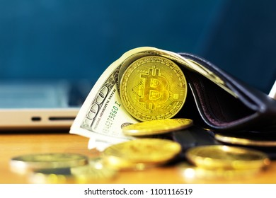 bitcoins whit money in black leather wallet near computer.