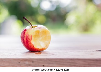Bite apple on wooden table with nature background.