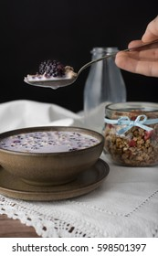 Bite of muesli with fruits on the silver spoon. Milky soup in brown bowl on white tablecloth.