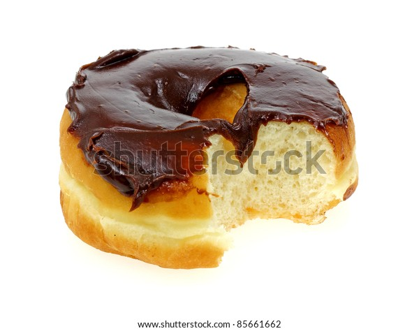 A bite of a plain raised donut with chocolate icing.