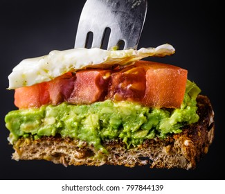 Bite sized piece of avocado toast with tomato and a fried egg on a fork.  Isolated on a black background