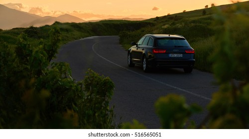 Bitola, Macedonia May 13, 2016 : Black Car Audi A6 with red lights standing on mountains road in twilight during sunset and mountains in background low light shot