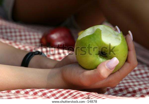 bitten apple held in hands at picnic