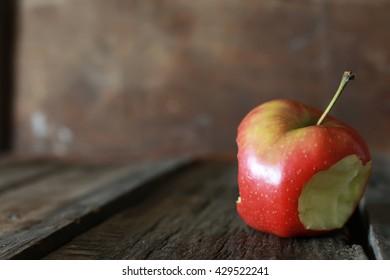 bitten apple on a wooden background
