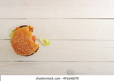 bitten bbq hamburger with vegetables, spices on wooden white background. Top view with copy space for text menu