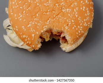 bitten big burger with cutlet cheese and tomato on a gray background