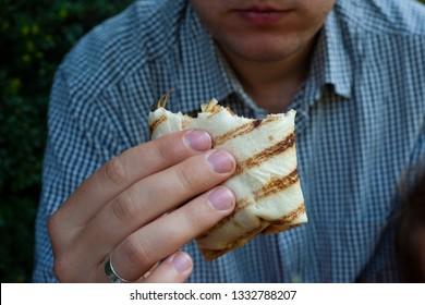 The bitten chicken wrap in the man hand.