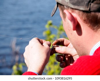 Bitten fishing lure. A guy checks up the bitten worm on a hook after the next pelting of fishing-rod. Close-up.