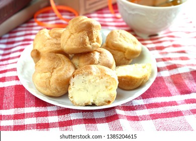 Bitten homemade small cakes profiterole choux pastry with custard next to a white cup with tea and books on a table with a rustic tablecloth in a red-white cage