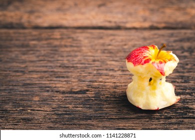 Bitten red apple on wood background