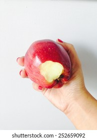 Bitten red apple in woman's hand on white background