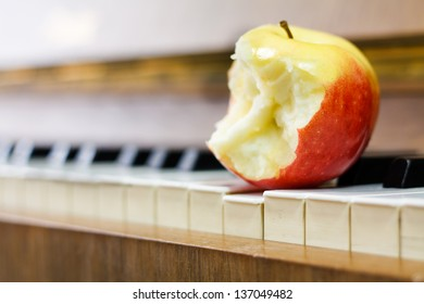 Bitten red and yellow apple on piano keys. Healthy or fresh music concept.