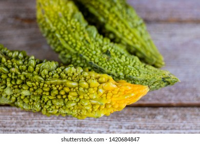 Bitter melon fresh organic green herb or vegetable, bitter cucumber or bitter cucumber on old wooden background with select focus