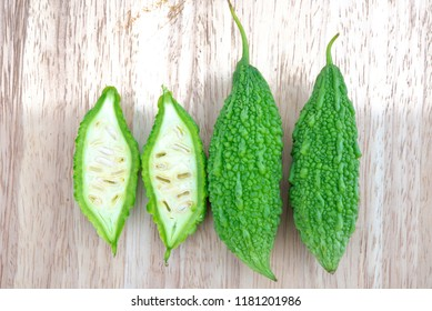 Bitter melon or Bitter gourd with half sliced on wooden background. bitter gourds.