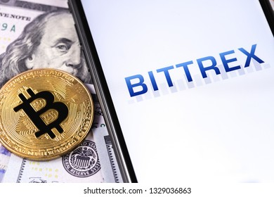 Bittrex cryptocurrency exchange website displayed on smartphone and stack of money, dollars, bitcoin. Moscow, Russia - March 1, 2019