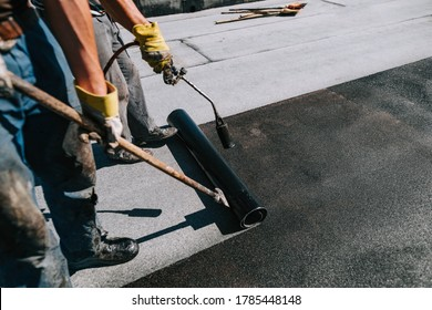 Bituminous membrane waterproofing system details and installation on flat rooftop. Professional construction worker  installing and waterproofing flat roof at house construction site.