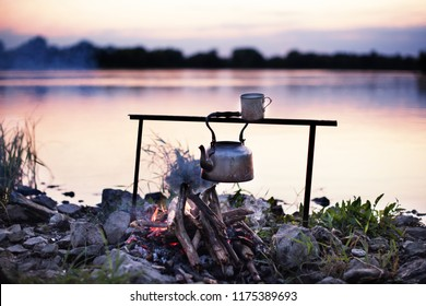 Bivouac on the river at sunset, with a water kettle hanging over the fire for tea and coffee. End of summer, goodbye to summer. A rocky shore with clumps of green grasses. The river Vistula in Poland.