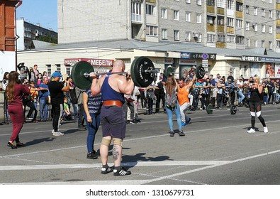 BIYSK, RUSSIA-CIRCA, JULY 2018: Strong athlete bodybuilder pumped strongman with a heavy body raises the bar in front of spectators on the street.
