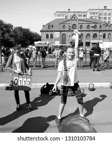 BIYSK, RUSSIA-CIRCA, JULY 2018: Young girl lifts a big weight dumbbell. City fesitwal sport on the street for a healthy lifestyle. Sports contests for arm-wrestling.