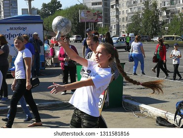 BIYSK, RUSSIA-CIRCA, JULY 2018: Young girl lifts a big weight dumbbell. City fesitwal sport on the street for a healthy lifestyle.