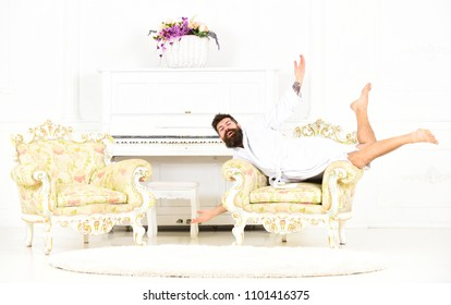 Bizarre bearded man posing in armchair. Odd guy lying on antique furniture. Millionaire in white hotel room.