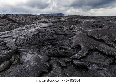 Bizarre formations on the lava fields of Puu Oo, Big Island Hawaii. The shiny rock consists of very fresh lava. The cone of Puu Oo is visible in the background.