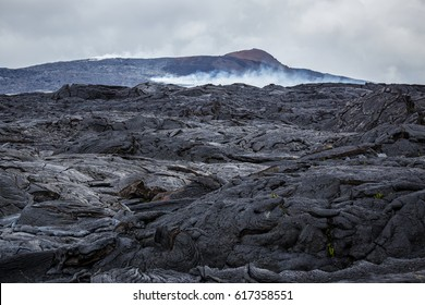 Bizarre formations of recent lava flows on Big Island Hawaii, which originate from Kilauea's crater Puu Oo, visible in the background.
