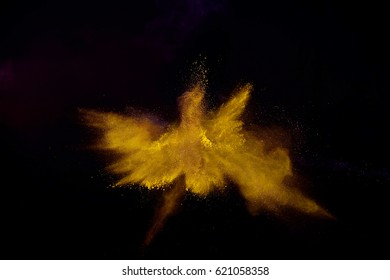 Bizarre forms of golden glitter powder paint explode in front of a black background to give off fantastic colors and forms.