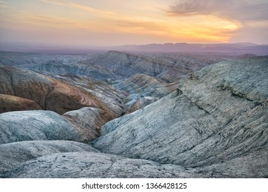 Bizarre layered mountains and Canyons at sunset in desert park Altyn Emel in Kazakhstan