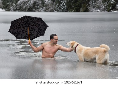 Bizarre picture of a man holiding an umbrella and petting a dog in a frozen lake. Taken in Alice Lake, Squamish, North of Vacouver, BC, Canada.