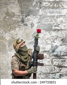 Bizarre soldier with a weapon and rose