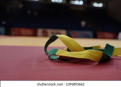 BJJ brazilian Jiujitsu competition green and yellow belt on the tatami mats at the tournament