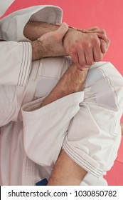 BJJ Brazilian jiu-jitsu training demonstration in traditional kimono. Breaking the grip with leg and arm
