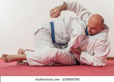 BJJ Brazilian jiu-jitsu training demonstration in traditional kimono. Going for Kimura lock from guard position