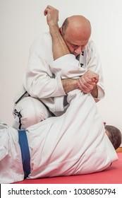 BJJ Brazilian jiu-jitsu training demonstration in traditional kimono. Squeezing elbow lock from Knee on Belly