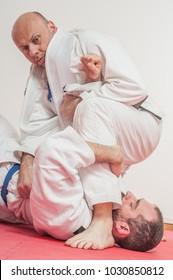 BJJ Brazilian jiu-jitsu training demonstration in traditional kimono. Going for Juji Gatame from Top position