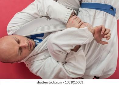 BJJ Brazilian jiu-jitsu training demonstration in traditional kimono. Kimura lock from guard, ude garami