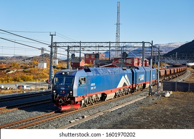 Bjornfjell, Norway - Sep 27, 2019: LKAB iron ore train loaded with iron ore pellets from the Kiruna mine in Sweden to the harbour in Narvik. Here passing by Bjornfjell station in Norway.