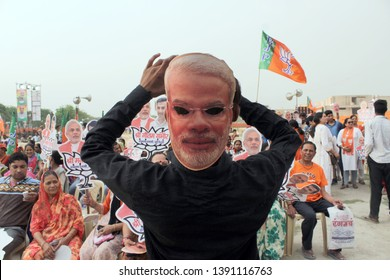 A BJP supporter wears a mask of Indian Prime Minister Narendra Modi during Rajnath Singh's election rally ahead of the Lok Sabha elections, at Shastri Park on May 1, 2019 in New Delhi, India.