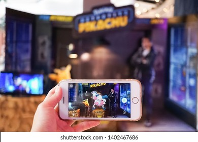 BKK - May 12, 2019: A photo of a hand holding smart phone playing Pokemon go AR mode with focus on Mr. Mime. Background is Pokemon Detective Pikachu standee to promote the movie. grained filter.