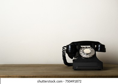 Black, 1940s vintage bakelite telephone at eye level on a wooden desk with ivory white wall as background providing copy space to the left.