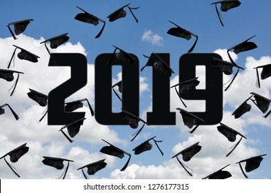 black 2019 graduation caps in summer sky with fluffy white clouds