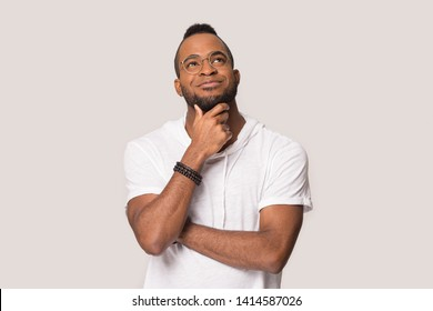 Black 30s guy in glasses touch beard daydreaming looks up posing isolated on grey studio background, mixed race man feels calm planning future, lost on positive thoughts, thinking and dreaming concept