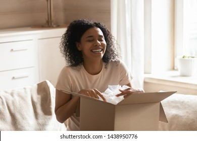 Black 30s woman received ordered goods online via internet website sitting on couch at home enjoy moment unpacking cardboard box parcel feels happy, commerce postal delivery, easy fast service concept