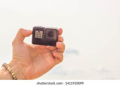 Black 4K action camera on beach