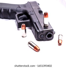 A black 9mm pistol with four 9mm hollow point bullets on and around it on a white background