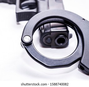 A black 9mm pistol with a black handcuff on it's muzzle on a white background