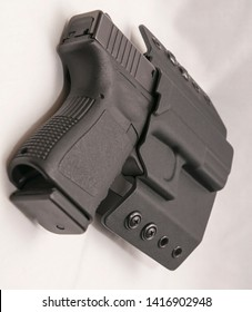 A black 9mm pistol in a black holster isolated on a white background